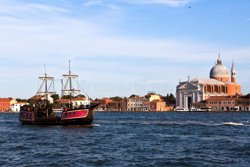 Pirat ship Redentore church, Venice, Italy. Pirat ship in the canals of Venice in front of the Redentore church or Chiesa del Santissimo Redentore, Venezia royalty free stock photo