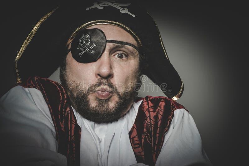 Pirata dell'uomo e sveglio con la toppa dell'occhio e vecchio cappello con i fronti divertenti e immagine stock libera da diritti