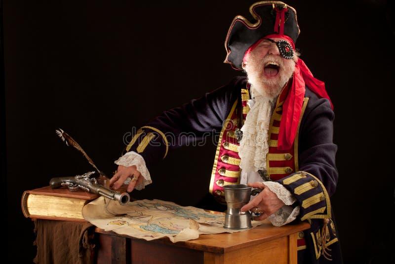 Pirata di risata con il programma del tesoro fotografia stock libera da diritti