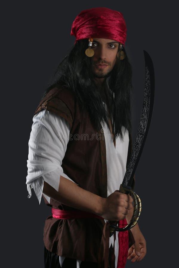 Pirata hermoso que sostiene una espada foto de archivo libre de regalías