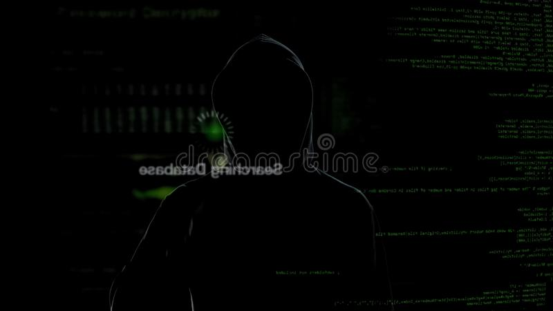 Pirata informático anónimo que mira la pantalla virtual, robando datos secretos, crimen cibernético foto de archivo libre de regalías