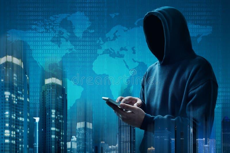 Pirata informático anónimo que usa el teléfono móvil fotografía de archivo
