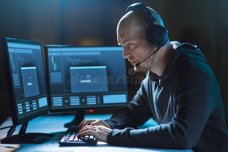 Pirata informático con el ordenador y las auriculares en sitio oscuro fotografía de archivo