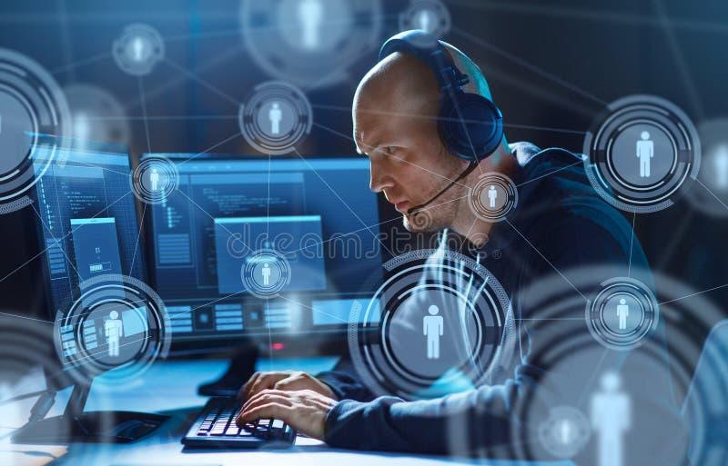 Pirata informático con el ordenador y las auriculares en sitio oscuro imagenes de archivo