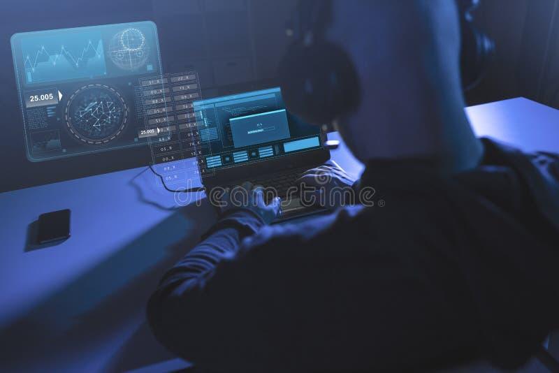 Pirata informático con la barra de progreso en el ordenador portátil en sitio oscuro fotografía de archivo