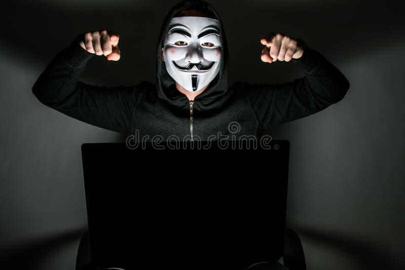 Pirata informático con la máscara anónima fotos de archivo