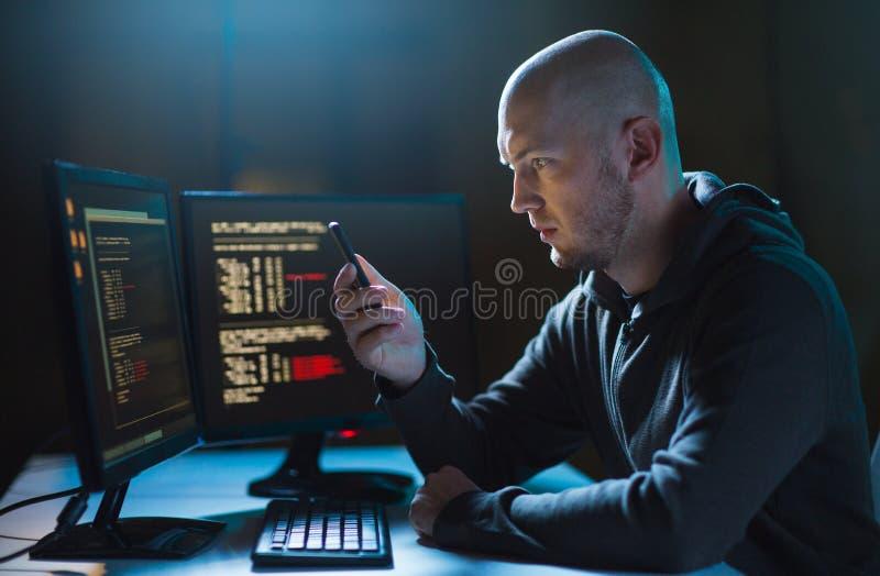 Pirata informático con smartphone y ordenadores en sitio oscuro imagen de archivo