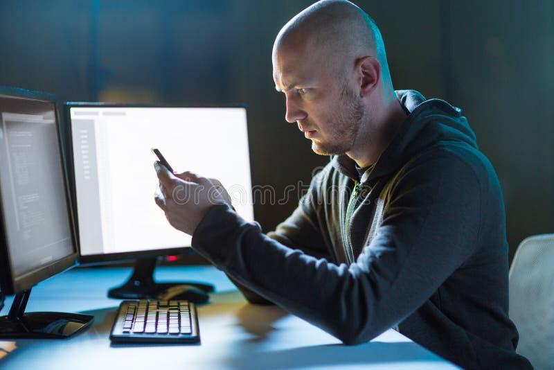 Pirata informático con smartphone y ordenadores en sitio oscuro fotografía de archivo