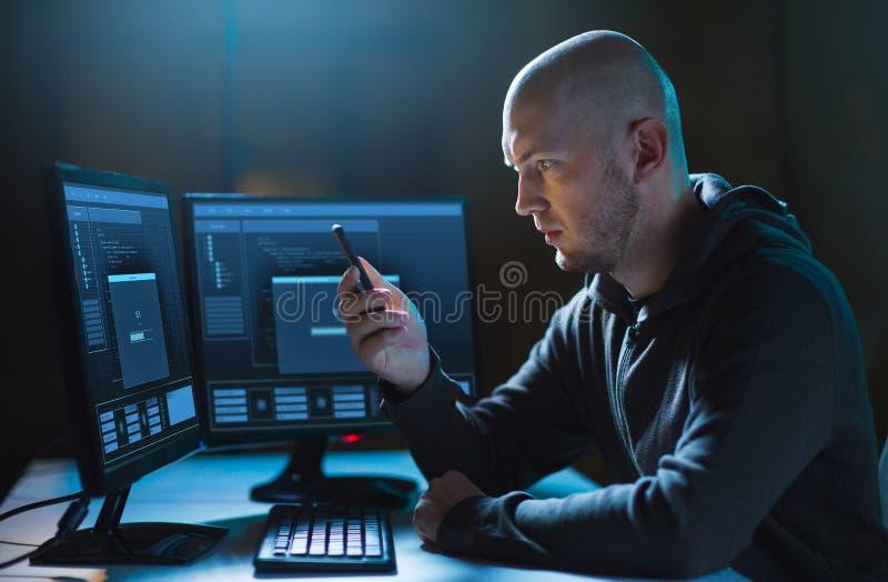 Pirata informático con smartphone y ordenadores en sitio oscuro foto de archivo
