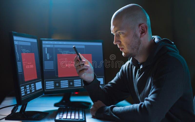Pirata informático con smartphone y ordenadores en sitio oscuro fotografía de archivo libre de regalías