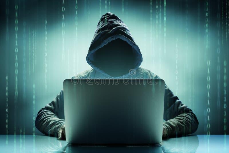 Pirata informático de ordenador anónimo anónimo con el ordenador portátil fotografía de archivo