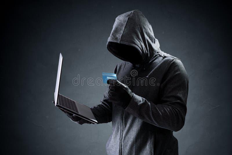Pirata informático de ordenador con la tarjeta de crédito que roba datos de un ordenador portátil imagen de archivo libre de regalías
