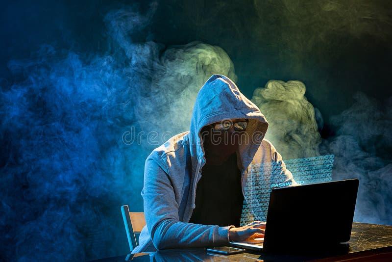 Pirata informático de ordenador encapuchado que roba la información con el ordenador portátil imagen de archivo libre de regalías