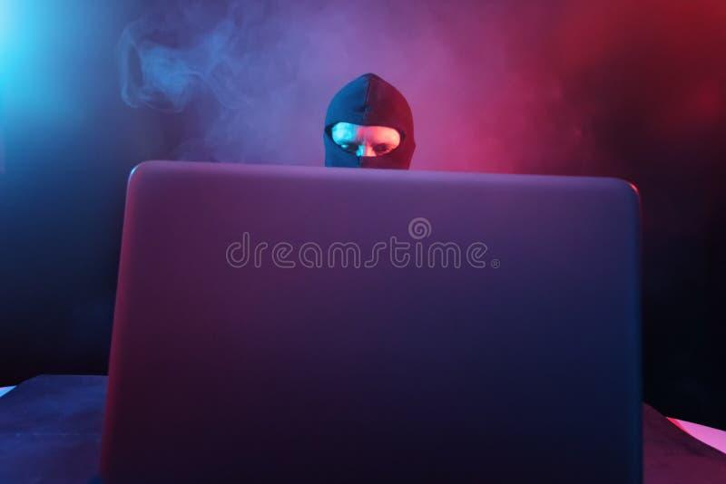 Pirata informático de ordenador enojado en traje que roba datos del illumina del ordenador portátil imagen de archivo