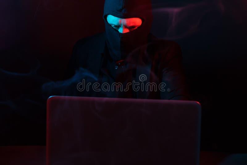 Pirata informático de ordenador enojado en traje que roba datos del illumina del ordenador portátil foto de archivo