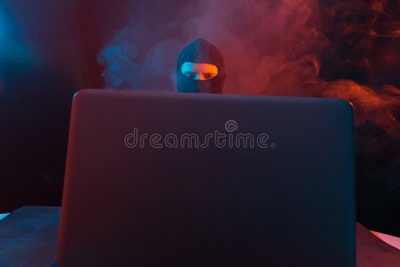 Pirata informático de ordenador enojado en traje que roba datos del illumina del ordenador portátil fotografía de archivo libre de regalías