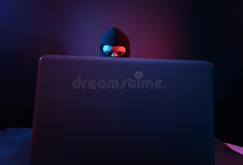 Pirata informático de ordenador enojado en traje que roba datos del illumina del ordenador portátil fotografía de archivo