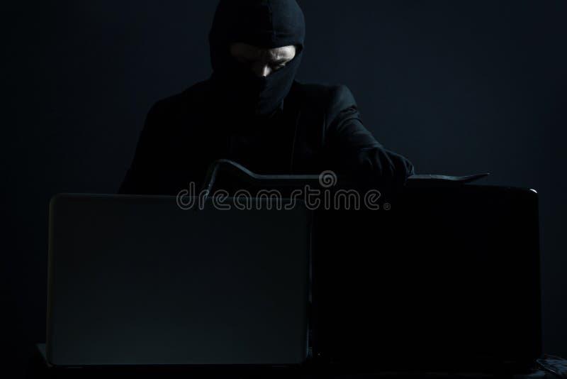 Pirata informático de ordenador enojado en traje que roba datos del ordenador portátil con la CRO (coordinadora) imagen de archivo