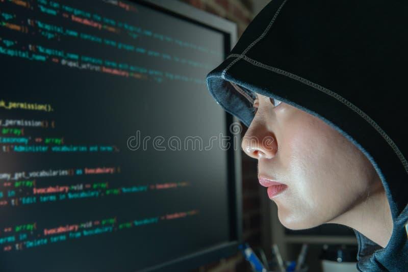 Pirata informático de sexo femenino que mira fijamente el monitor seriamente fotos de archivo libres de regalías