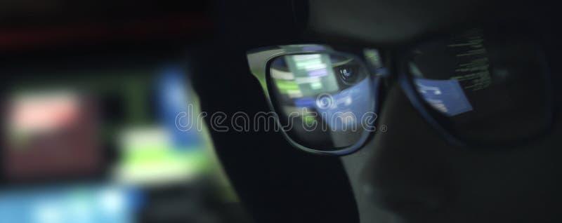 Pirata informático del empollón con los vidrios en la oscuridad foto de archivo libre de regalías