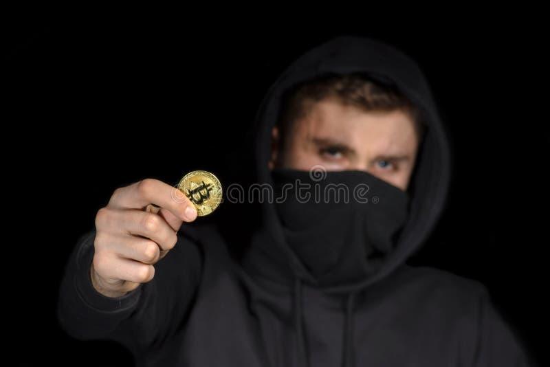 Pirata informático del primer con el bitcoin borroso del control de la cara a disposición que inicia el ataque cibernético, se imagen de archivo