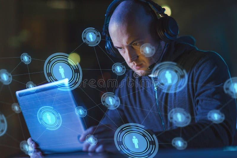 Pirata informático en auriculares que mecanografía en el ordenador portátil en sitio oscuro fotos de archivo libres de regalías