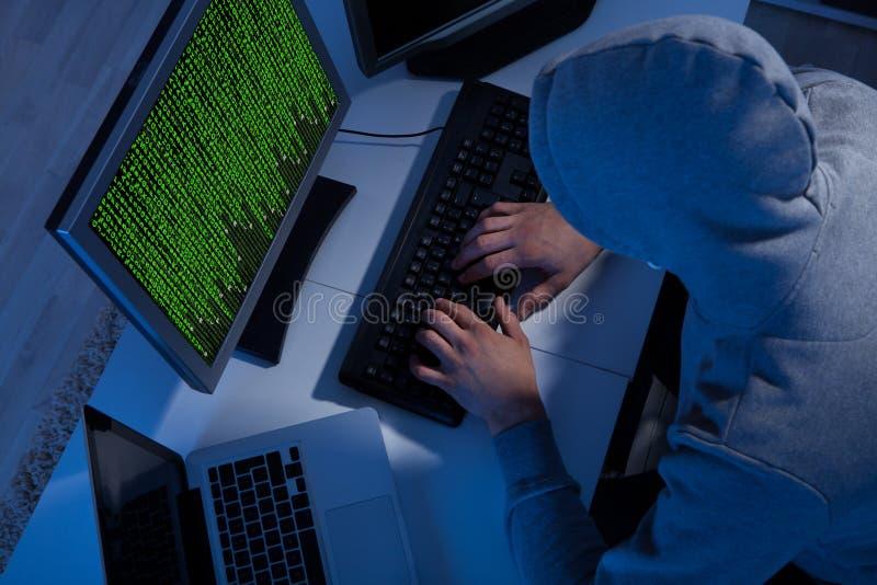 Pirata informático en chaqueta con capucha usando el ordenador en la tabla foto de archivo