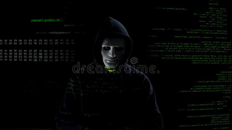 Pirata informático en la máscara blanca que consigue lista para trabajar, sistema que ataca con código del malware imagen de archivo libre de regalías