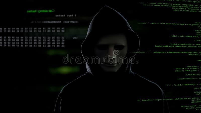 Pirata informático en la máscara blanca que roba la información importante del attentado terrorista del servidor imagenes de archivo