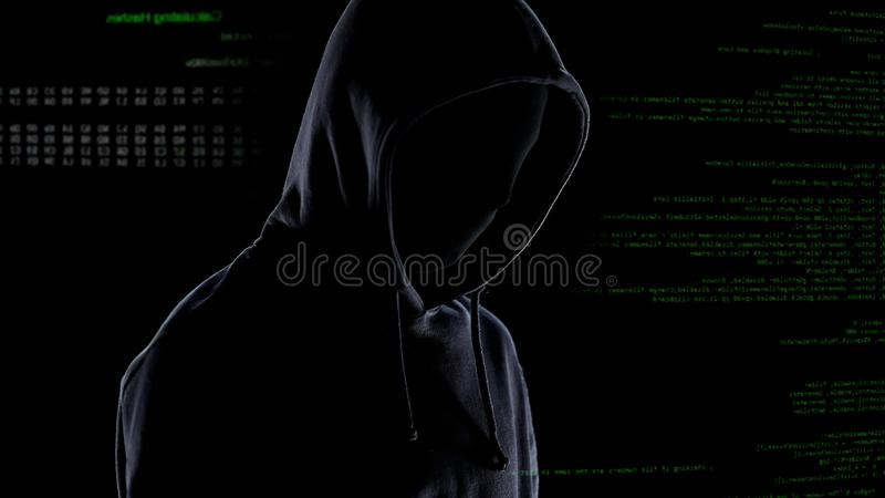 Pirata informático en máscara y sudadera con capucha en el fondo del código de ordenador, ciberdelincuencia de planificación fotos de archivo libres de regalías