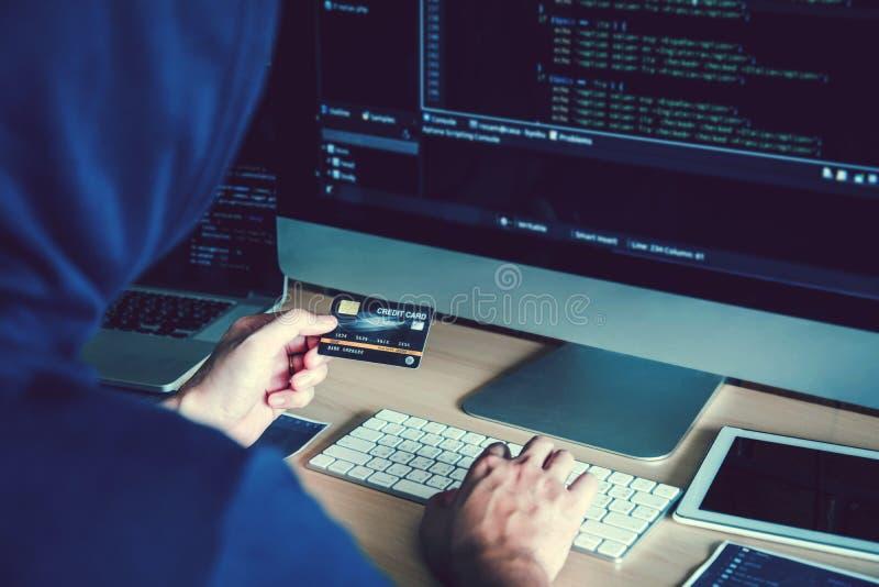 Pirata informático encapuchado peligroso que usa la tarjeta de crédito que mecanografía malos datos en sistema en línea del orden fotos de archivo libres de regalías