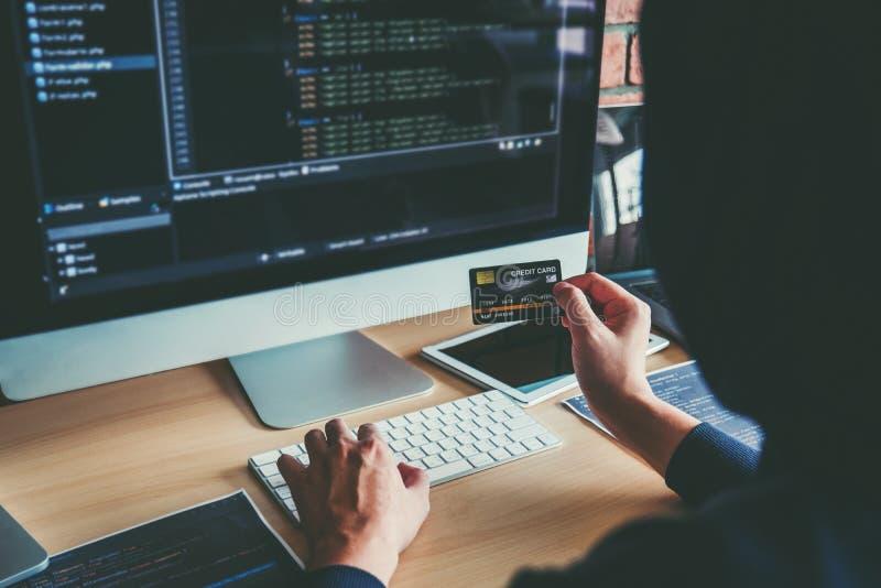 Pirata informático encapuchado peligroso que usa la tarjeta de crédito que mecanografía malos datos en sistema en línea del orden imágenes de archivo libres de regalías