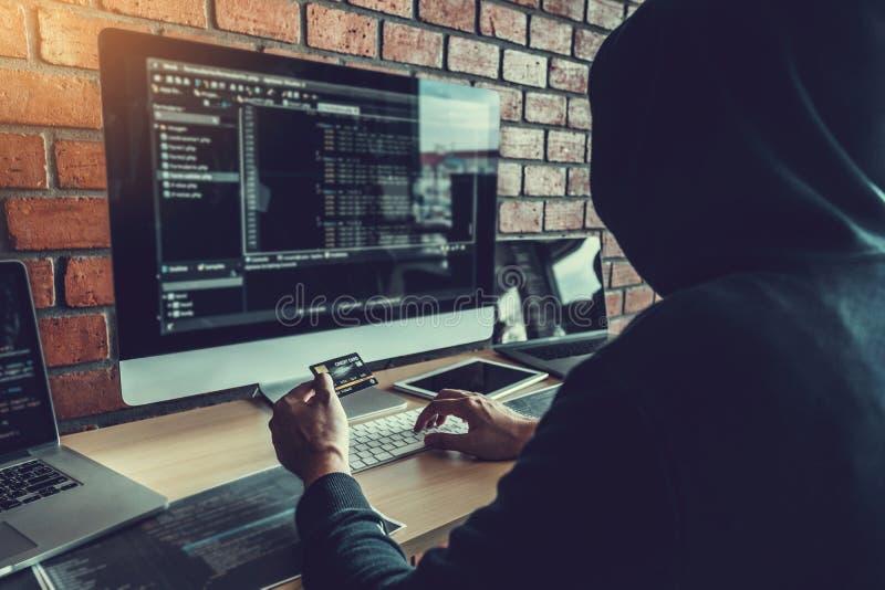 Pirata informático encapuchado peligroso que usa la tarjeta de crédito que mecanografía malos datos en sistema en línea del orden imagen de archivo