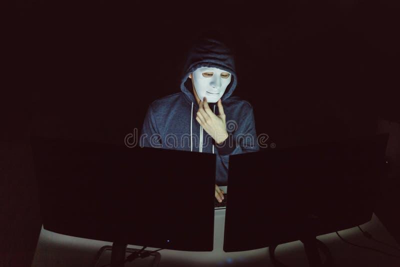 Pirata informático enmascarado debajo de la capilla usando el ordenador a cortar en sistema e intentar confiar delito informático imagenes de archivo