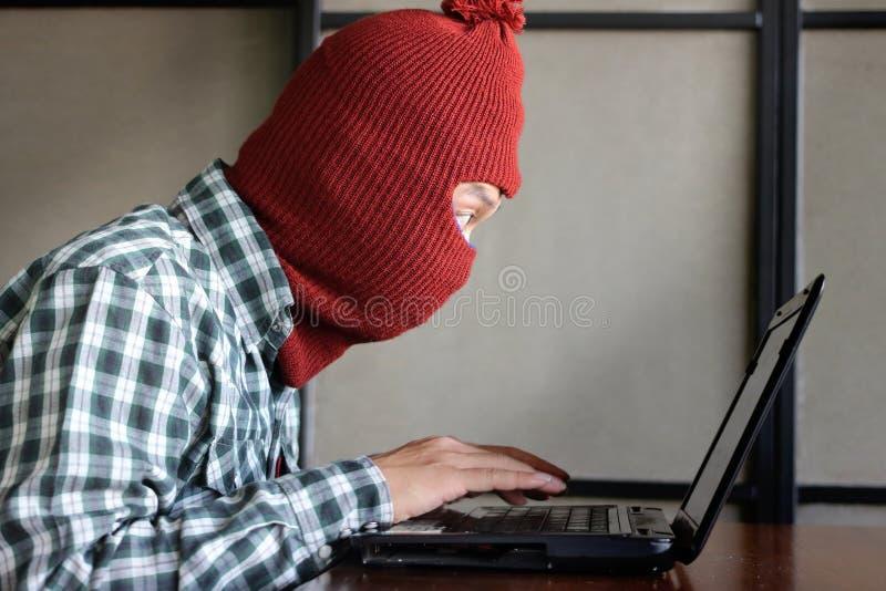 Pirata informático enmascarado que lleva un pasamontañas con el ordenador portátil que roba datos de la importancia Concepto del  imágenes de archivo libres de regalías
