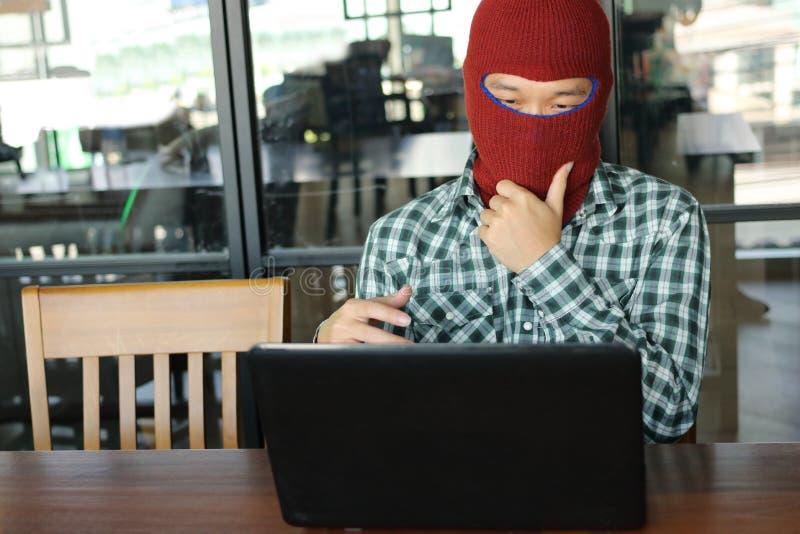 Pirata informático enmascarado que lleva un pasamontañas que mira un ordenador portátil y que roba datos de la información import foto de archivo libre de regalías
