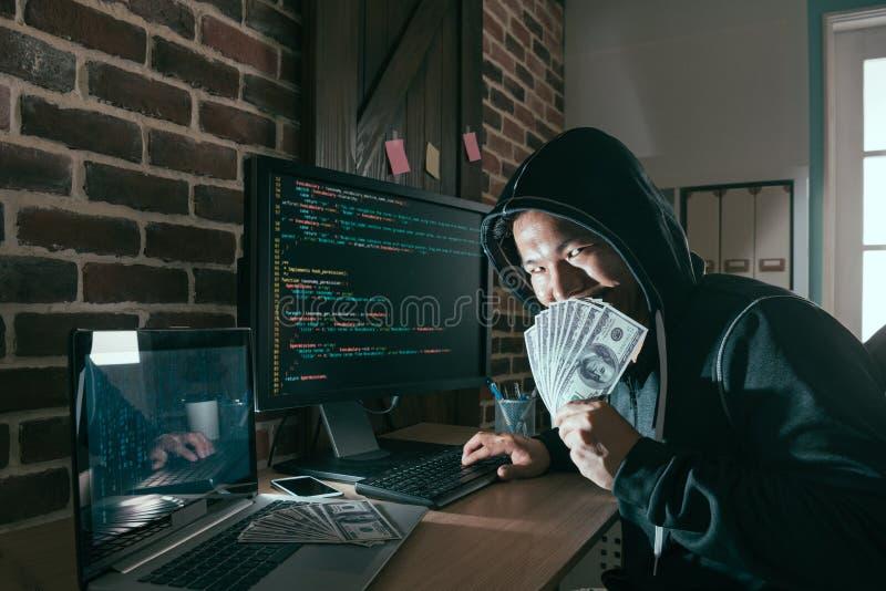 Pirata informático malvado que sostiene la cara de la cubierta del billete de banco del efectivo fotografía de archivo libre de regalías