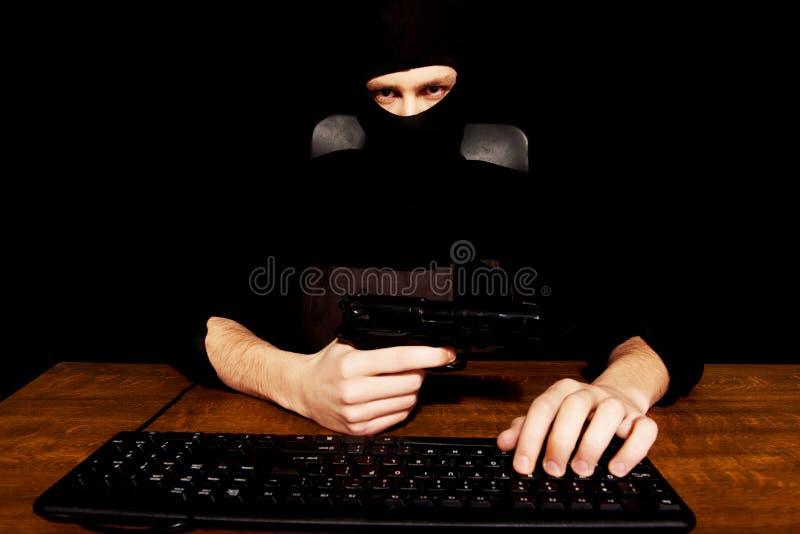 Pirata informático peligroso en el pasamontañas que sostiene el arma imagen de archivo libre de regalías