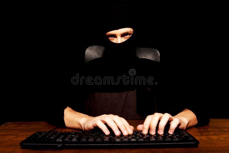 Pirata informático peligroso en pasamontañas negro fotos de archivo