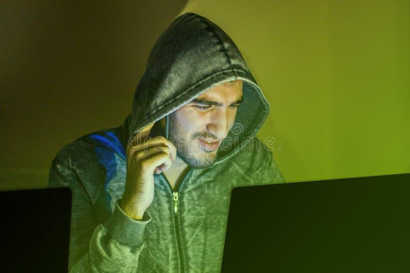 Pirata informático que habla en el teléfono imágenes de archivo libres de regalías