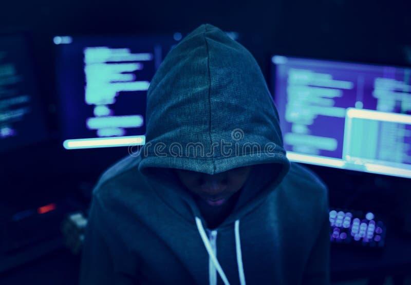 Pirata informático que lleva una sudadera con capucha con los ordenadores en el fondo imagenes de archivo