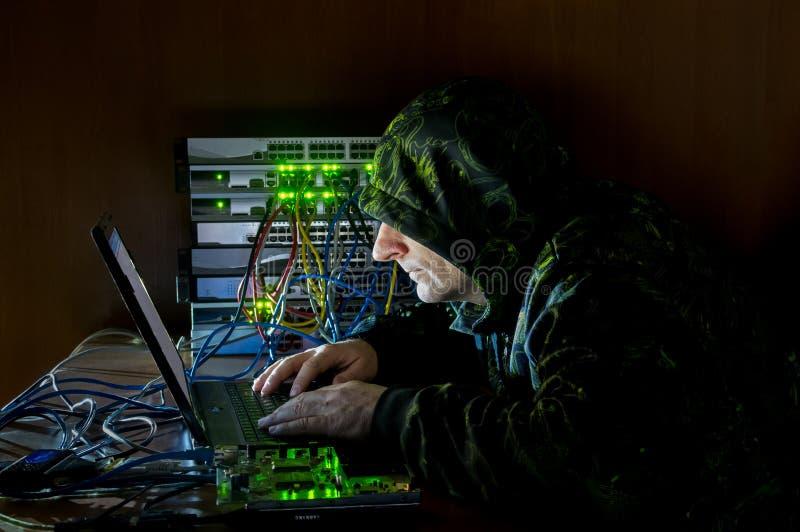 Pirata informático que trabaja en el ordenador con las herramientas de hackers fotografía de archivo libre de regalías