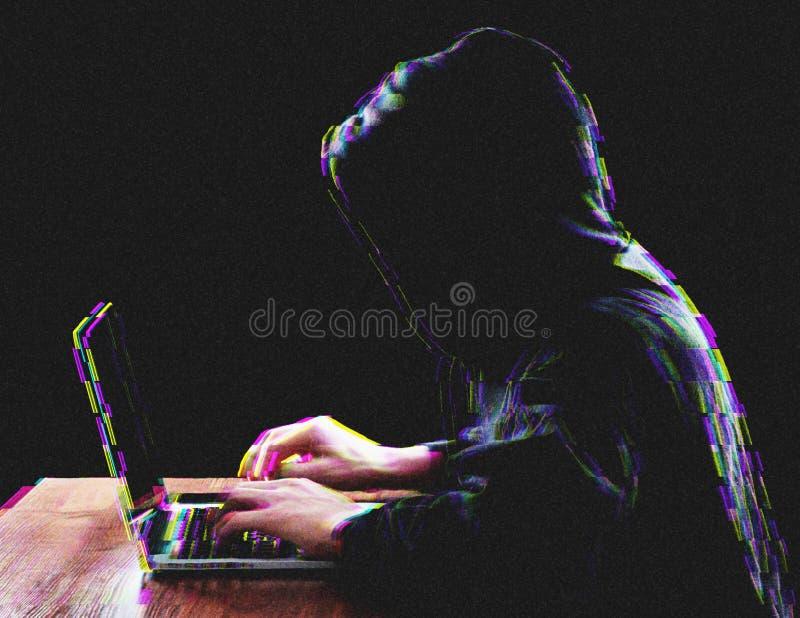 Pirata informático que usa el ordenador portátil para el ataque de organización en los servidores corporativos imagen de archivo libre de regalías