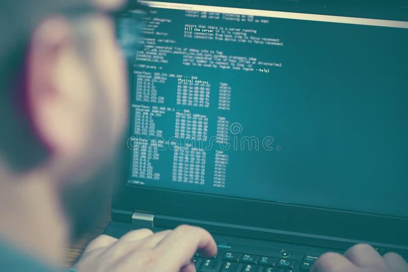 Pirata informático que usa la computadora portátil Porciones de dígitos en la pantalla de ordenador fotos de archivo