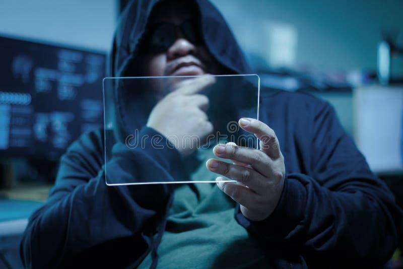 Pirata informático que usa la tableta de cristal clara en blanco con los proces de la oscuridad y del grano imagen de archivo