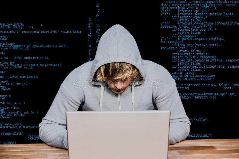 pirata informático que usa su ordenador portátil contra líneas de la orden imagenes de archivo