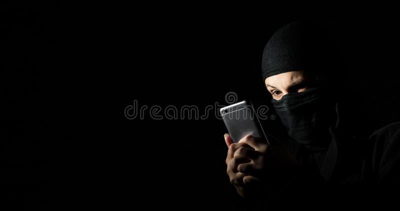 Pirata informático usando el teléfono elegante Muchacha adulta joven en ropa negra con miradas ocultadas de la cara en la pantall imagen de archivo libre de regalías