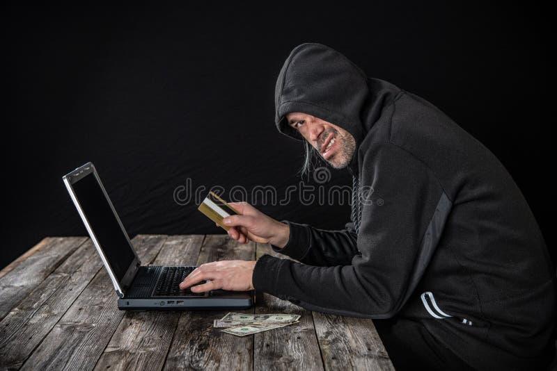Pirata inform?tico en sudadera con capucha negra con el ordenador port?til, notas de la tarjeta de banco y del d?lar imagen de archivo libre de regalías