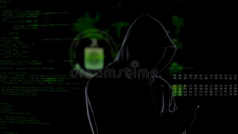 Pirata inform?tico encapuchado irreconocible an?nimo que usa smartphone para robar los datos, ciberdelincuencia imagen de archivo