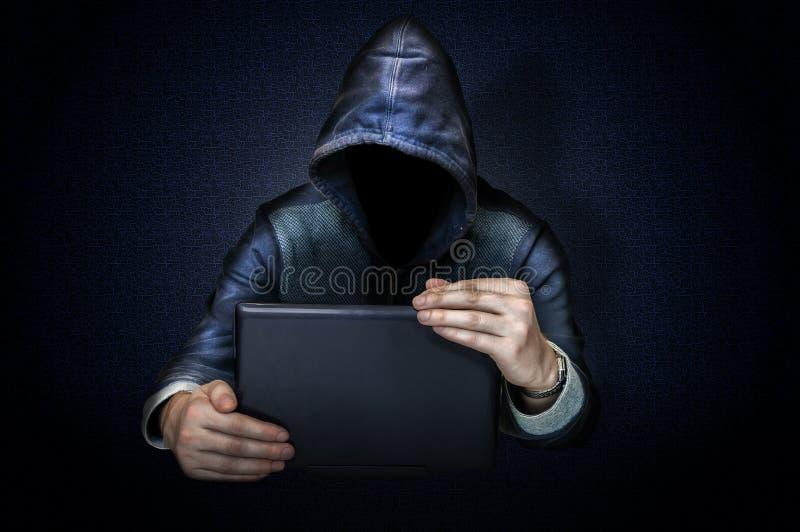 Pirata informatico anonimo con il computer portatile fotografia stock